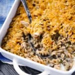 A casserole dish of tuna noodle casserole with a spoon scooping it out.