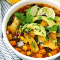 Close up photo of a bowl of vegetarian tortilla soup with avocado, sweet potato, cilantro, and lime.