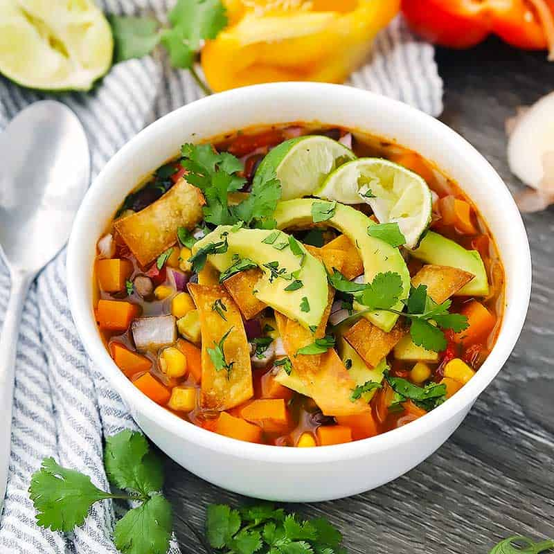 This healthy vegetarian tortilla soup (also, vegan!) is packed with flavor and loaded with veggies, sweet potatoes, black beans, and thickened using masa (corn flour). This is the perfect vegan gluten free recipe for cold weather!