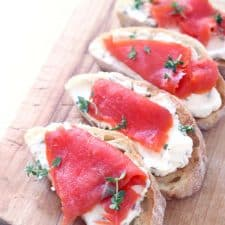 A row of four cream cheese and salmon toasts on a wooden cutting board.