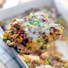 A piece of chicken and corn enchilada casserole being lifted out of a white casserole dish.