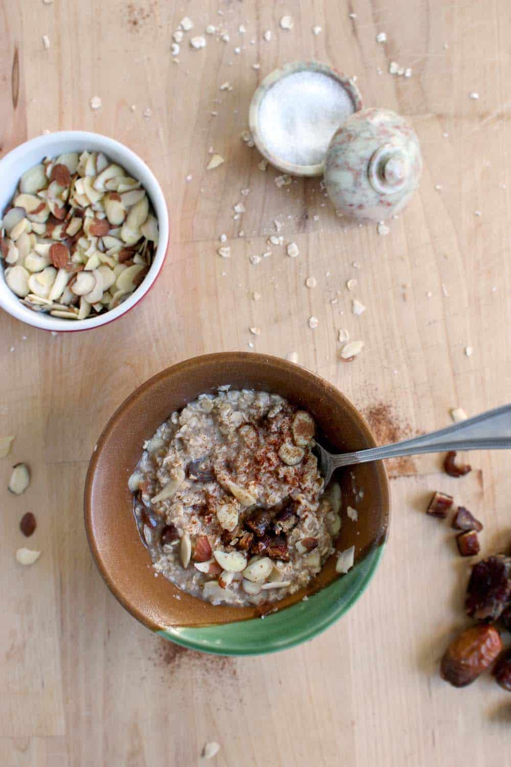 Bird's eye view of a brown ceramic bowl of oatmeal with a spoon sticking out, and ingredients like slivered almonds and white sugar scattered around.