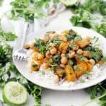 Side view of moroccan butternut squash and chickpea stew on a bed of white rise, on a white plate, with a fork perched on the side and herbs scattered around.
