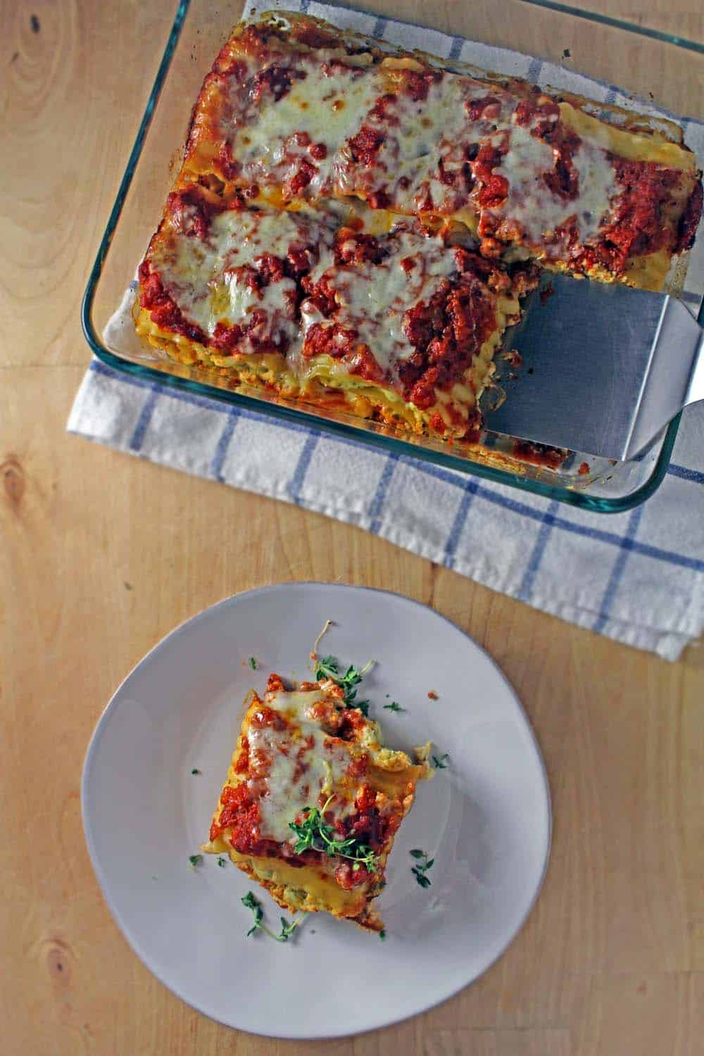 Bird's eye vide of a glass casserole holding chicken pesto lasagna roll ups and a white plate holding a piece.