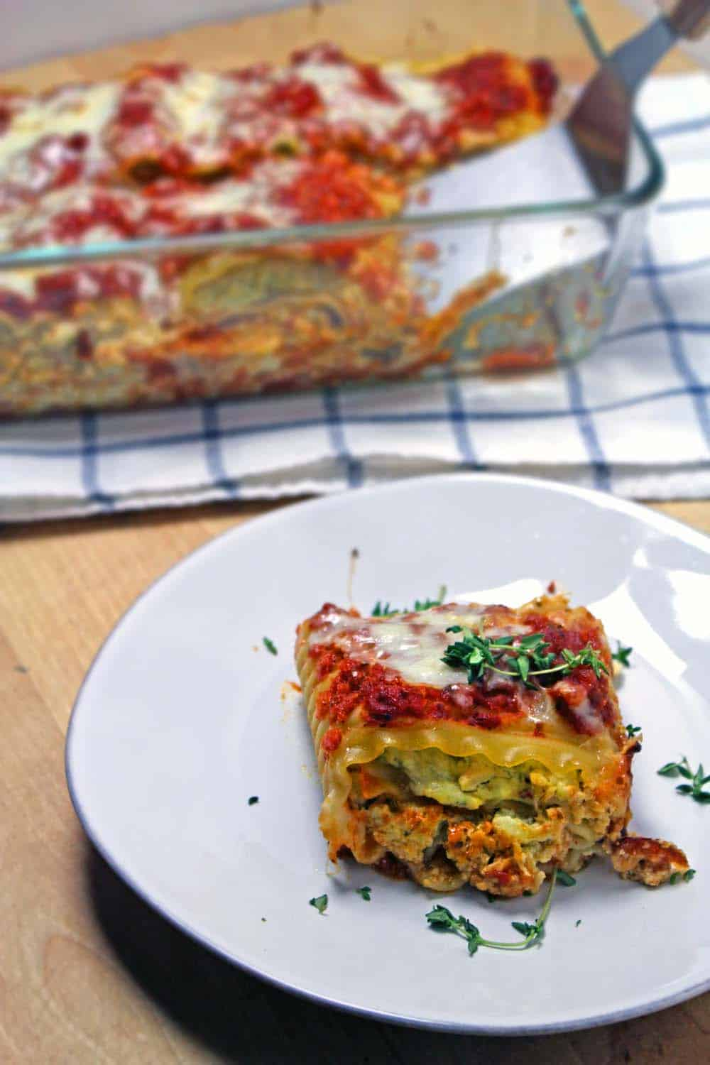 A piece of pesto chicken lasagna roll-up in the foreground on a white plate, with a glass casserole holding the rest of the dish in the background.