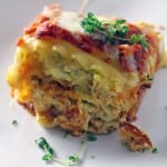 A pesto chicken lasagna roll up on a white plate.