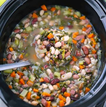 A ladle in a slow cooker with 15 bean soup.