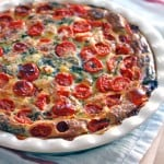 Crustless spinach, tomato, and feta quiche in a white pie dish and on a white cloth with red stripes.