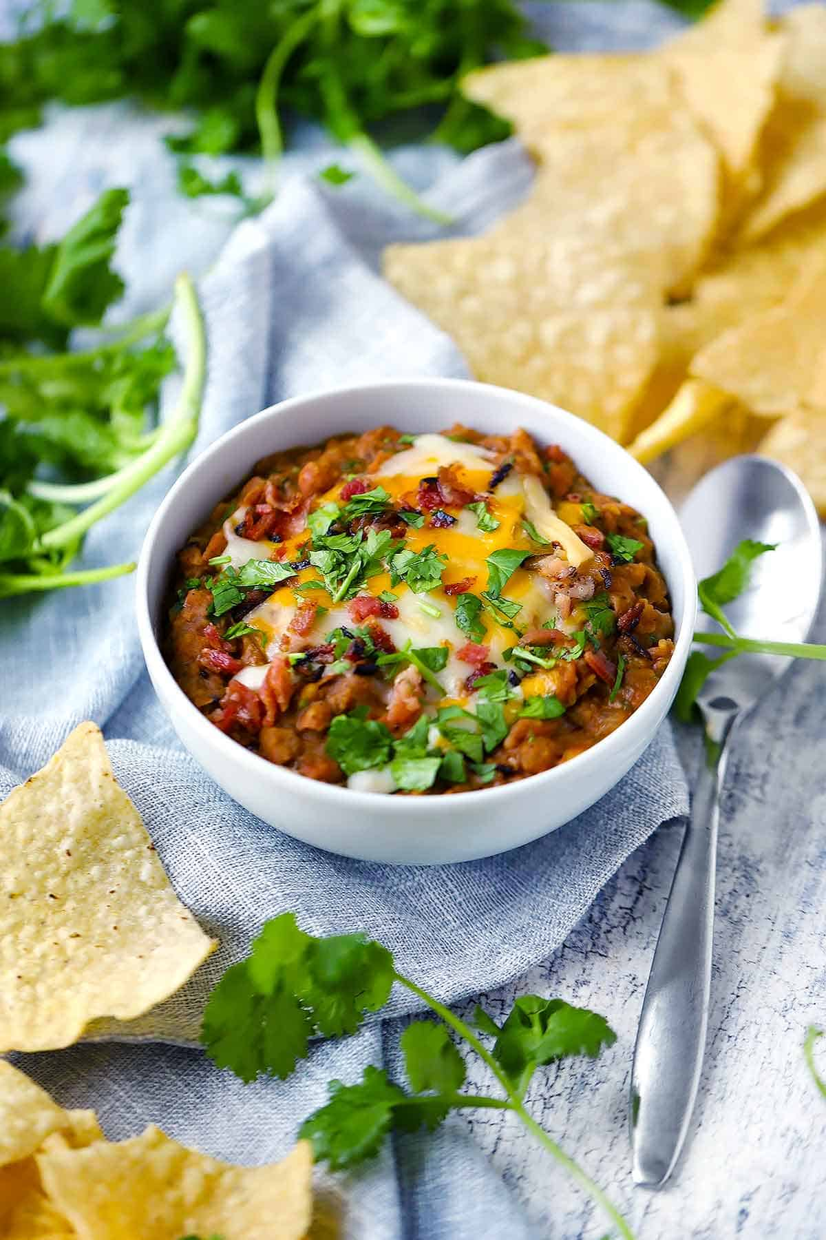Photo collage showing the steps to making refried beans: sautéing onions, browning ingredients, the skillet with beans added, and the skillet with the beans mashed.
