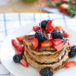 Stack of four pancakes on a white plate, topped with berries and a stream of maple syrup drizzling onto the pancakes from outside of the photo frame.