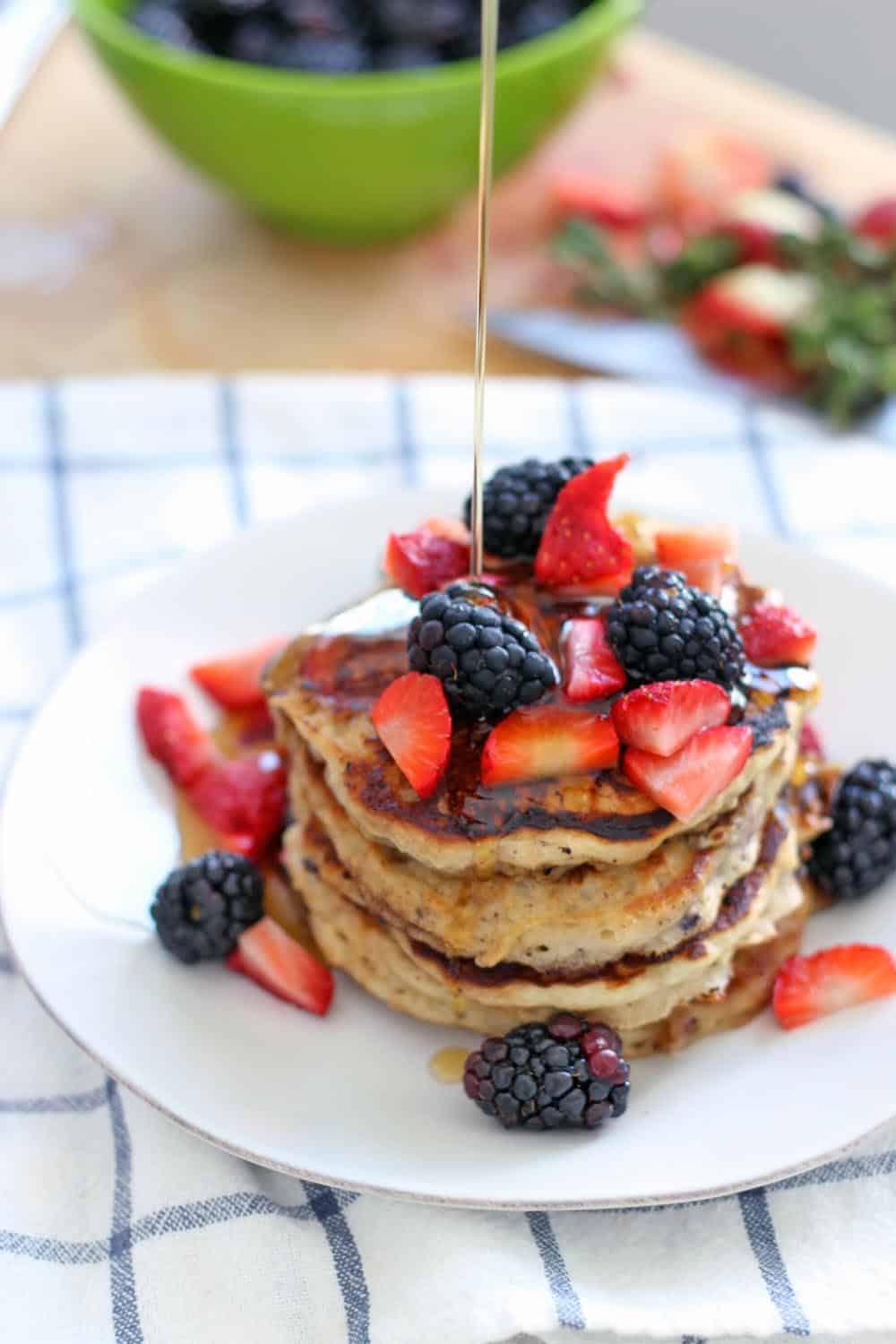 These berry oat pancakes are the fluffiest pancakes you'll ever have, and are made with 100% whole grains! Freeze the leftovers for a quick weekday breakfast.
