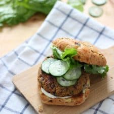 Veggie burger with the top bun pushed aside to show toppings, on a wooden cutting board, on a blue and white checkered cloth.