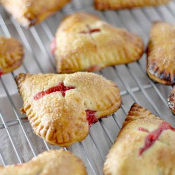 Several strawberry ginger hand pies on a wire cooling rack.