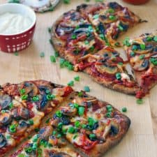 Two Buffalo mushroom naan pizzas on a wooden cutting board, each cut into fourths, with chopped scallions and ingredients scattered around.