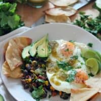 White plate holding fried eggs, tortilla chips, sliced avocado, and black beans, all garnished with fresh herbs.