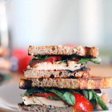 Two sandwich halves stacked on top of each other on a white plate. Mozzarella, tomato, basil, and balsamic glaze fill each sandwich half.