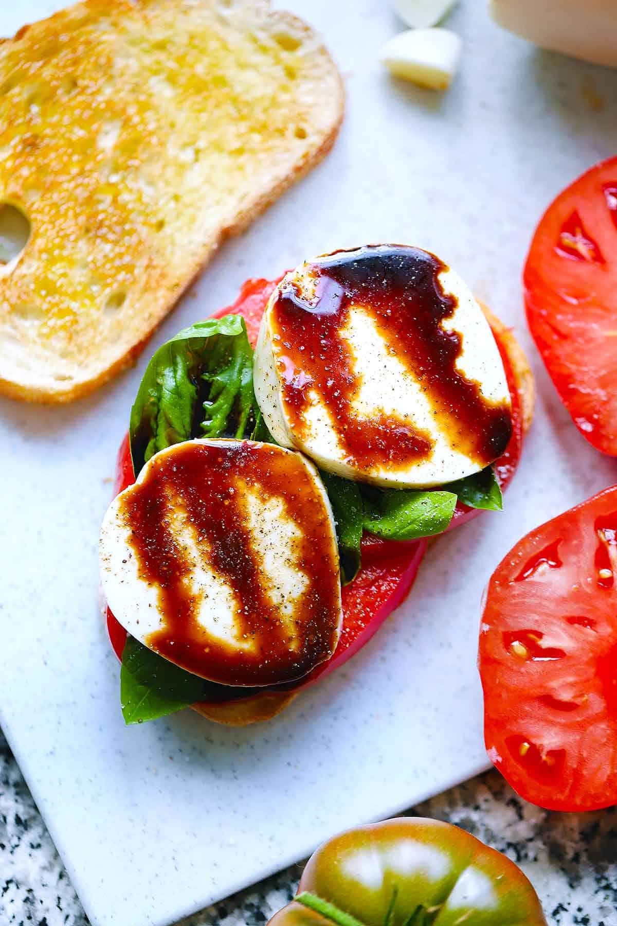 Two slices of bread with mozzarella, tomato, basil, and balsamic glaze topping the bread. More ingredients are in the background.
