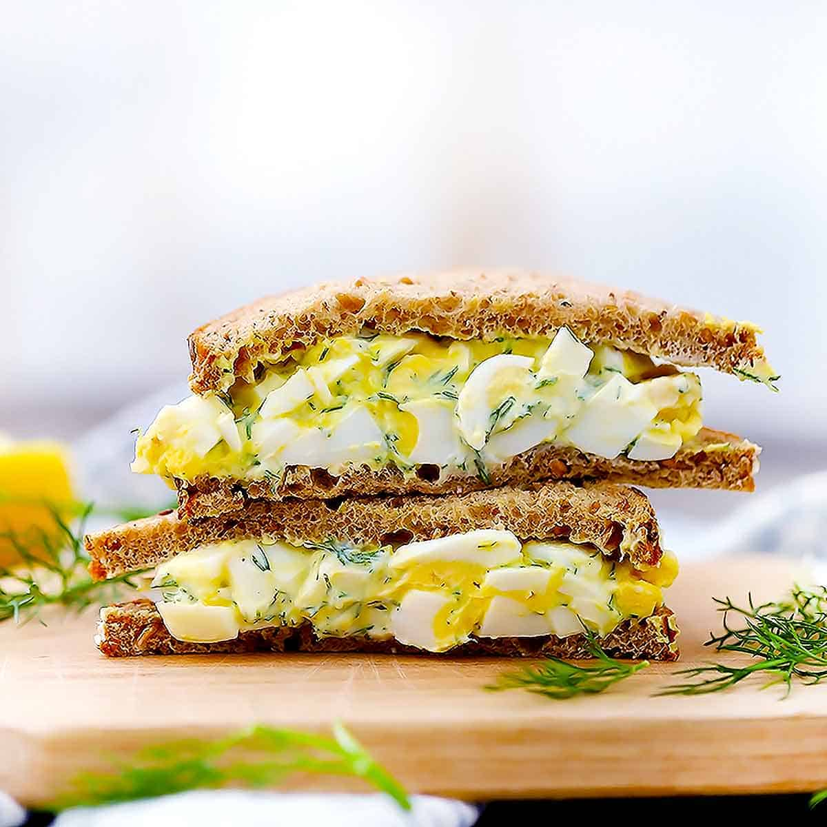 An egg salad with dill sandwich stacked on top of each other.