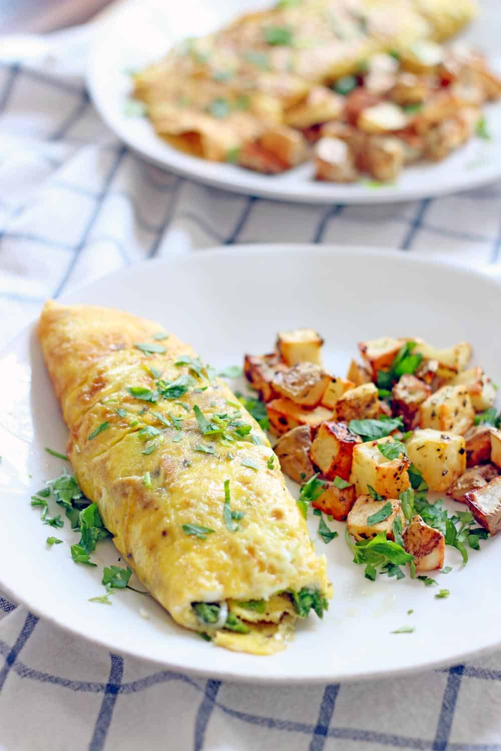 White plate holding Spring omelette with a side of cubed, roasted potatoes, and sprinkled with chopped herb garnish.