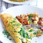 White plate holding Spring omelette with a fork piercing into the omelette, next to a side of roasted, cubed potatoes.