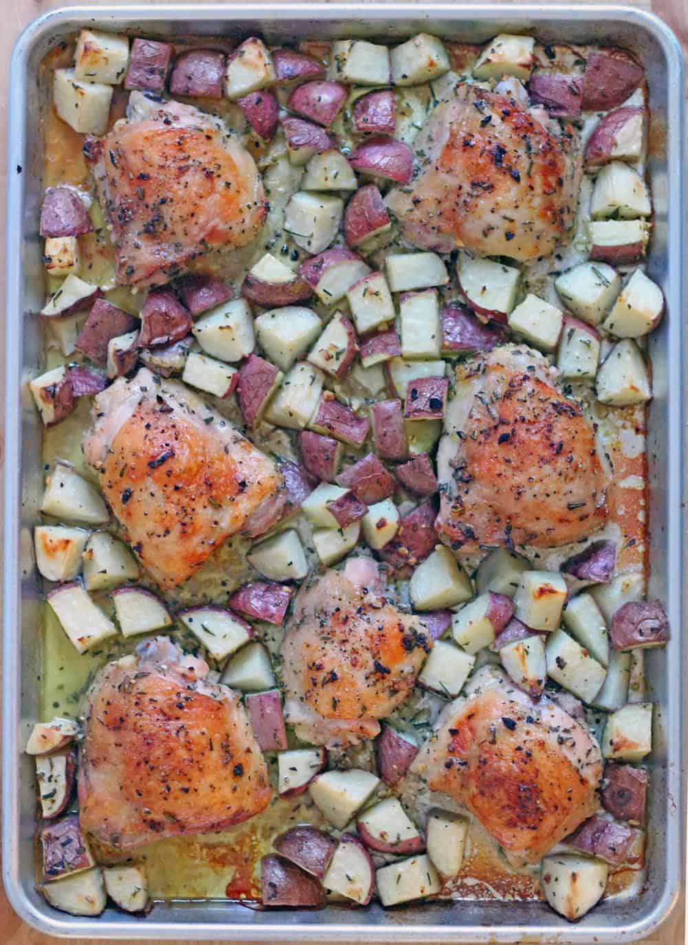 Bird's eye view of a baking sheet holding Roast Chicken and Potatoes Sheet Pan Dinner.