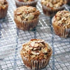Several muffins spread out on a wire baking sheet.