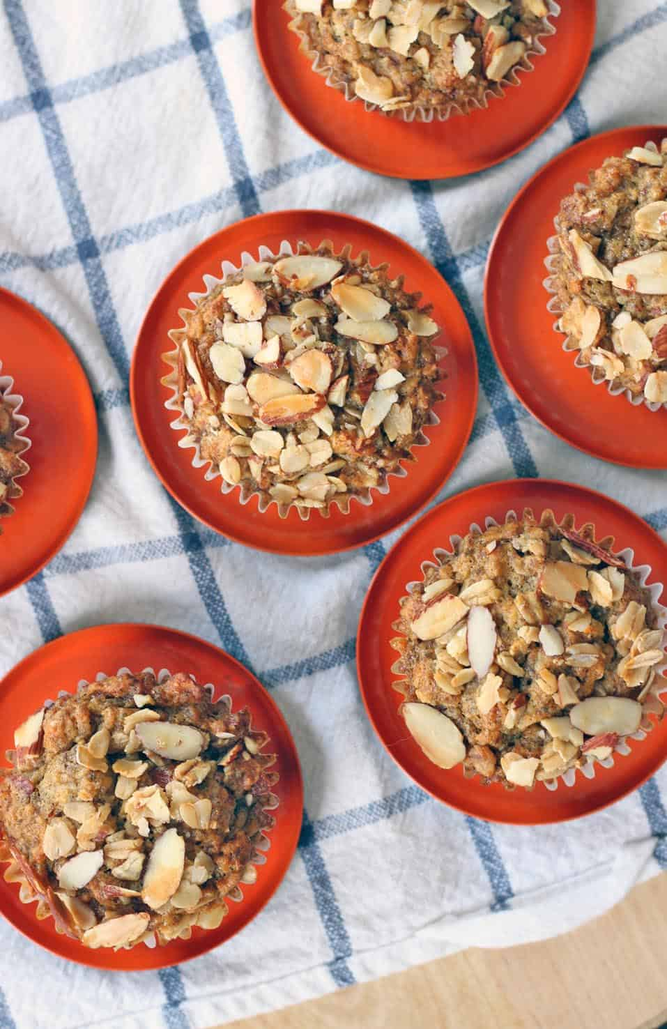 Bird's eye view of Maple Banana Oat and Nut Muffins on individual red saucers, all on a blue and white checkered cloth.