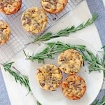 Bird's eye view of a white plate holding three mini quiches, next to a wire cooling rack holding several more mini quickes. Sprigs of rosemary are scattered around.