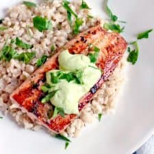 Bird's eye view of a white plate holding a salmon filet on top of a bed of brown rice, with a dollop of Avocado Lemon and Garlic Aioli on the sauce. The meal is sprinkled with chopped herbs.
