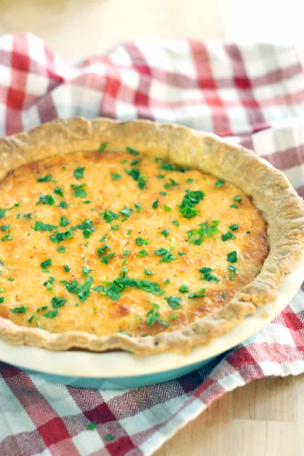 Whole Spicy Southern Tomato and Spinach Pie in a ceramic pie dish, on a red and white checkered cloth.