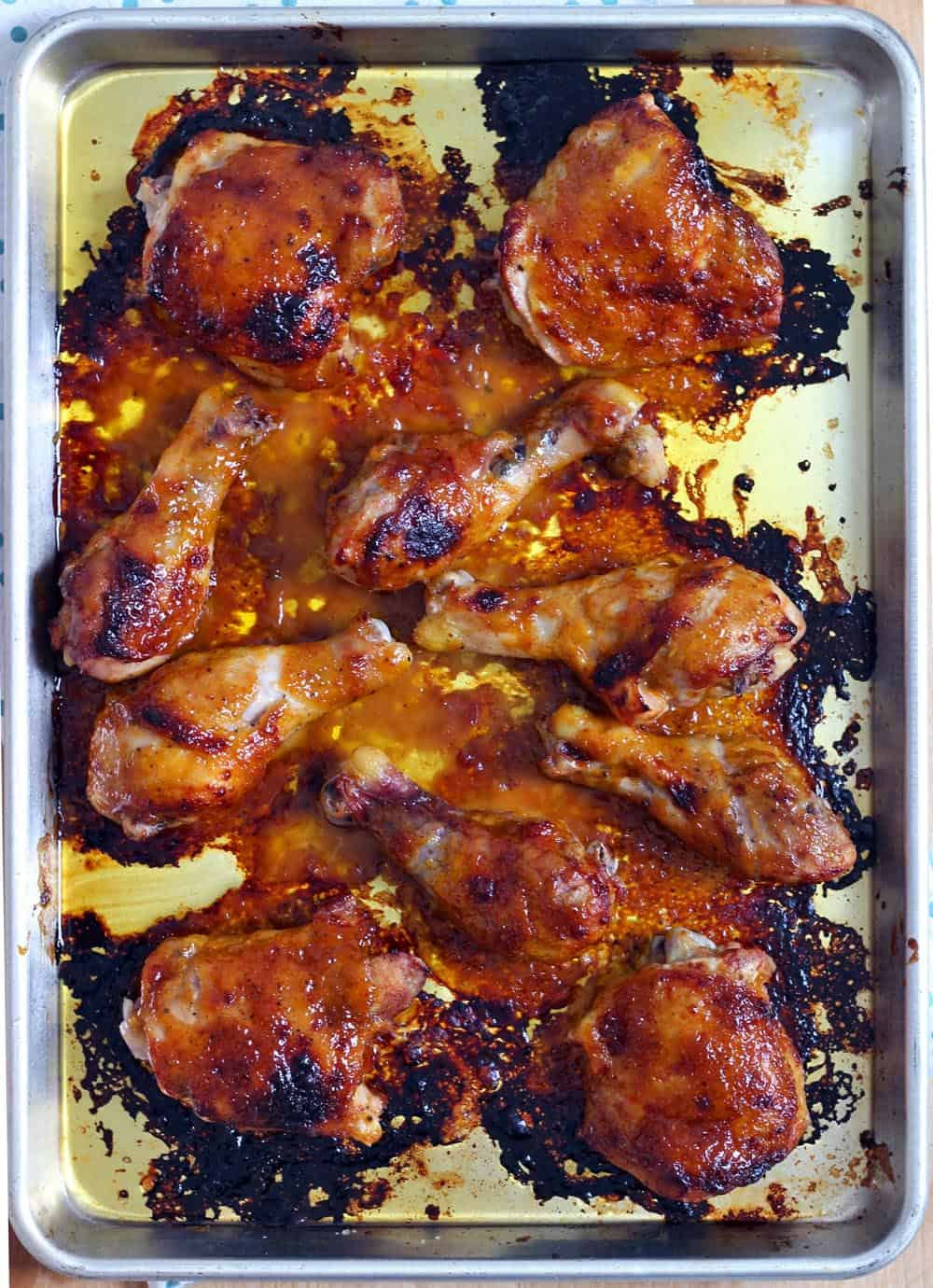 A roasting pan holding several pieces of cooked bbq chicken.