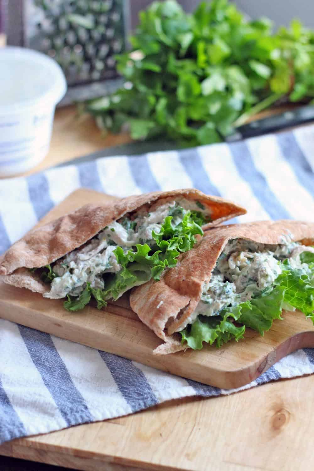 A pita pocket stuffed with tzatziki chicken salad on a striped towel.