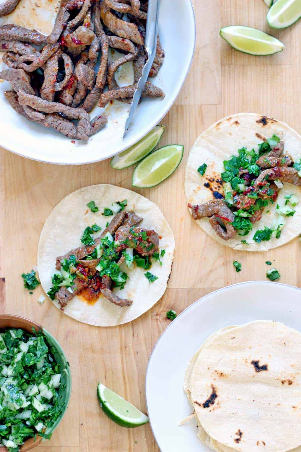 Bird's eye view of a wooden cutting board holding two open tacos, a plate of tortillas, a plate of steak, lime wedges, and chopped greens.
