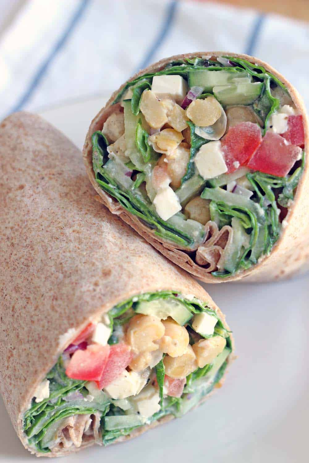 Close-up of the inside of two halves of Mediterranean Chickpea and Feta Salad Wrap with Creamy Greek Dressing.