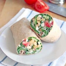 Two halves of a wrap filled with greens, chickpeas, tomatoes, feta, and other fillings, displayed on a white plate, on a blue and white striped cloth. Ingredients are in the background.