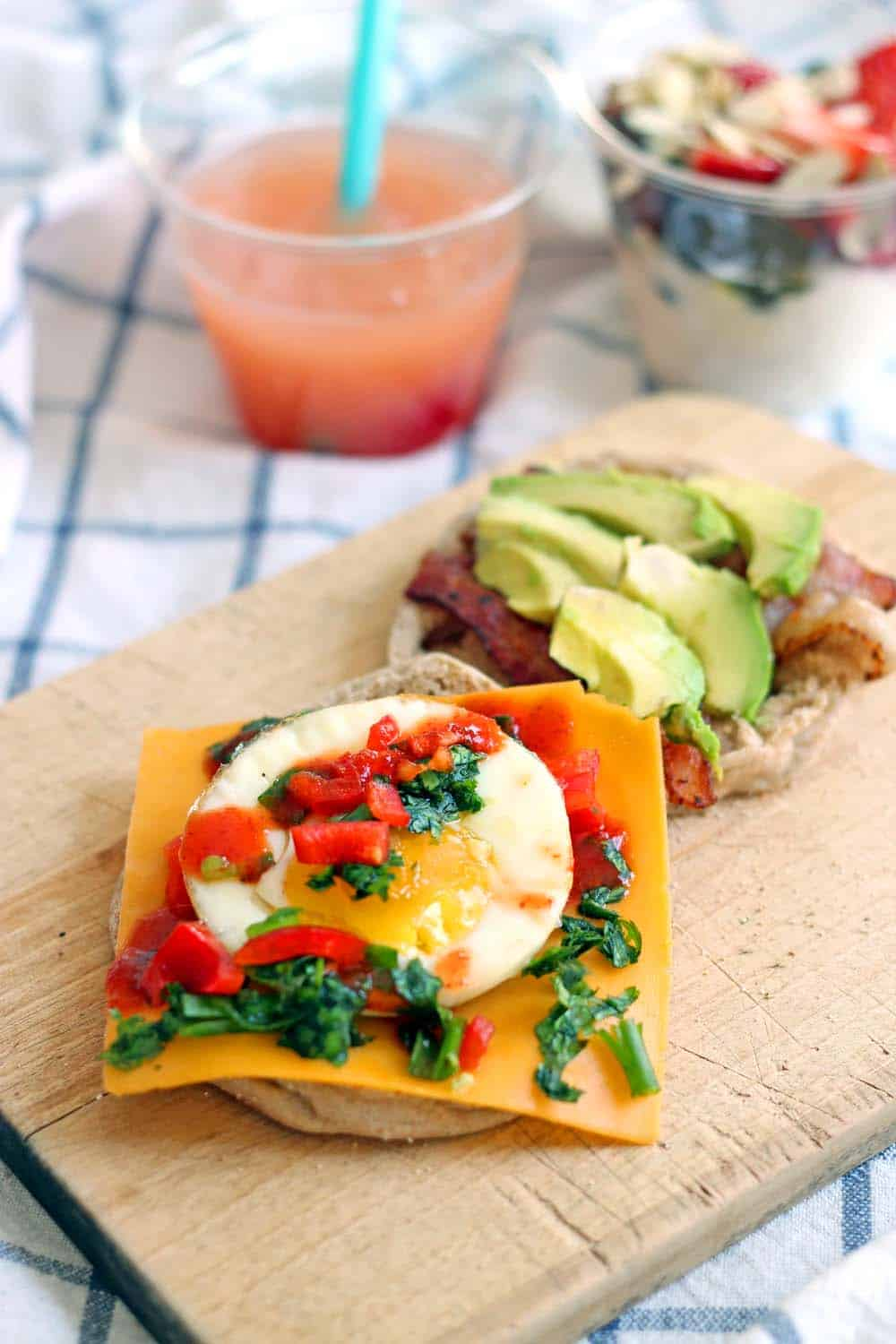 Breakfast sandwich with eggs, cheese, bacon, aliced avocado, and chopped vegetable toppings on a wooden cutting board.