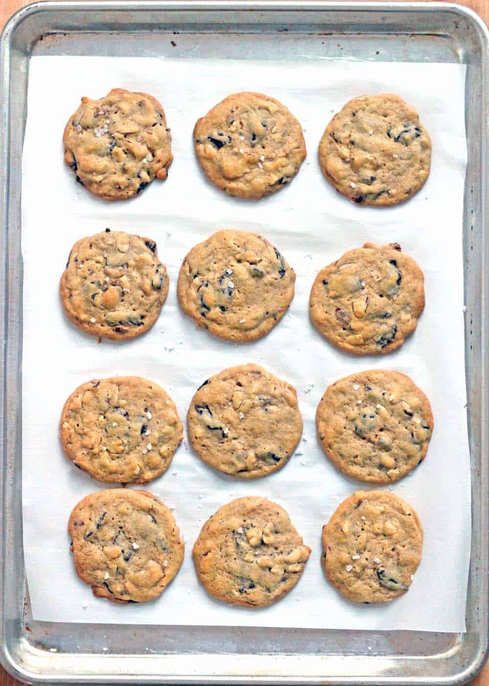 Bird's eye view of a baking sheet lined with parchment paper, holding 12 cookies spread out in rows.