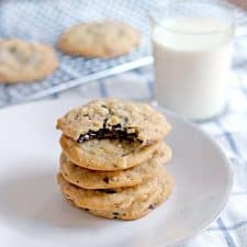 Five cookies stacked on a white plate. The top cookie has a bite taken out of it, and reveals chocolate on the inside.
