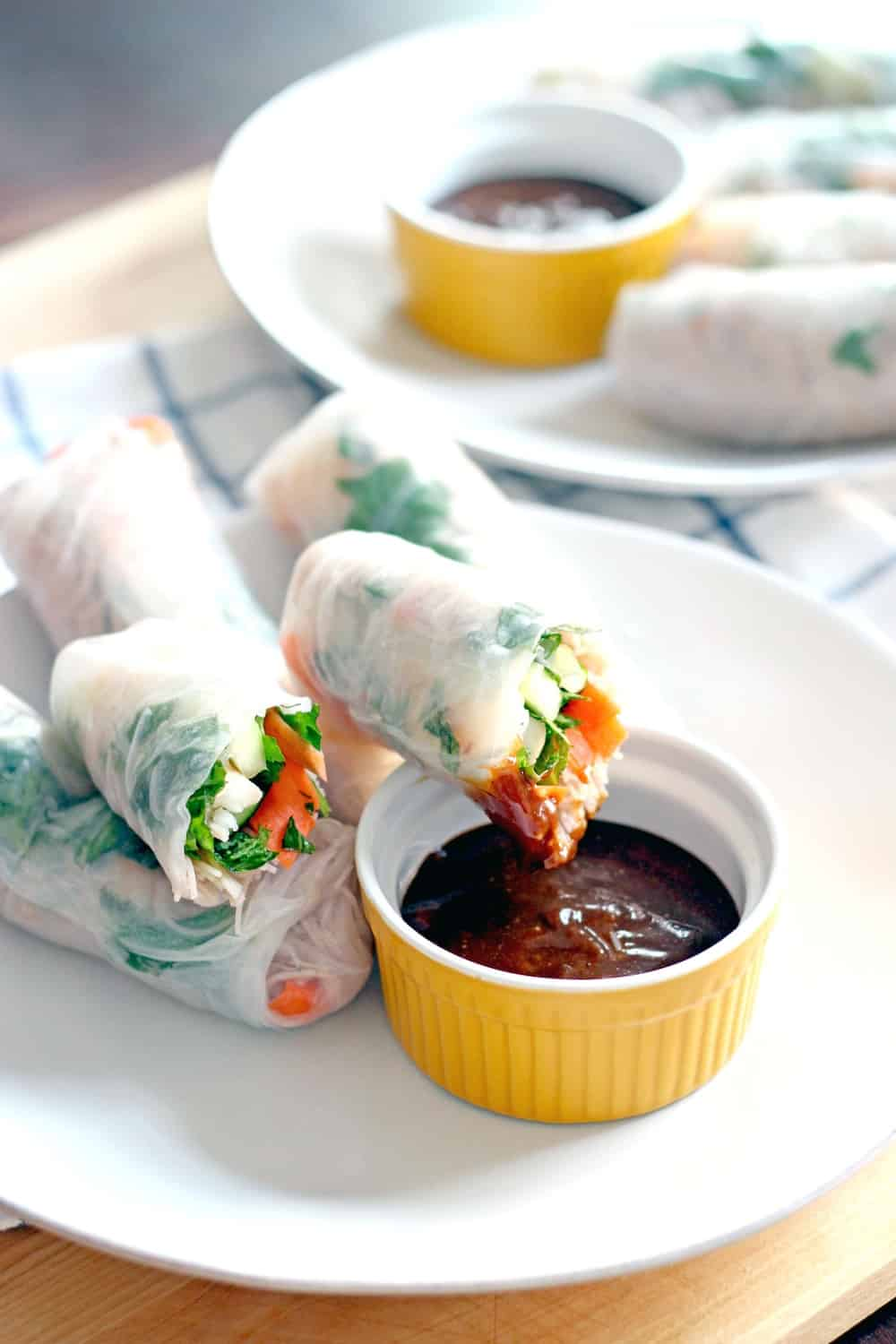 A white plate holding a few fresh spring rolls and a ramekin of dark brown sauce. One of the spring rolls is perched on the edge of the ramekin and partially dipped in sauce.