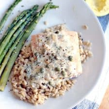 Bird's eye view of white plate holding Garlic Poached Salmon with Creamy Lemon Caper Sauce over rice, with asparagus on the side.