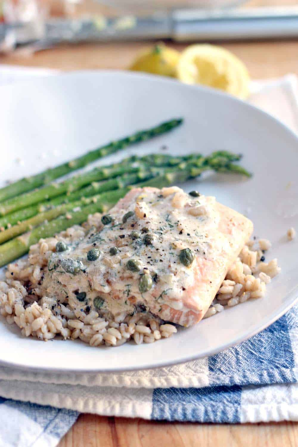 White plate holding Garlic Poached Salmon with Creamy Lemon Caper Sauce over rice, with asparagus on the side.
