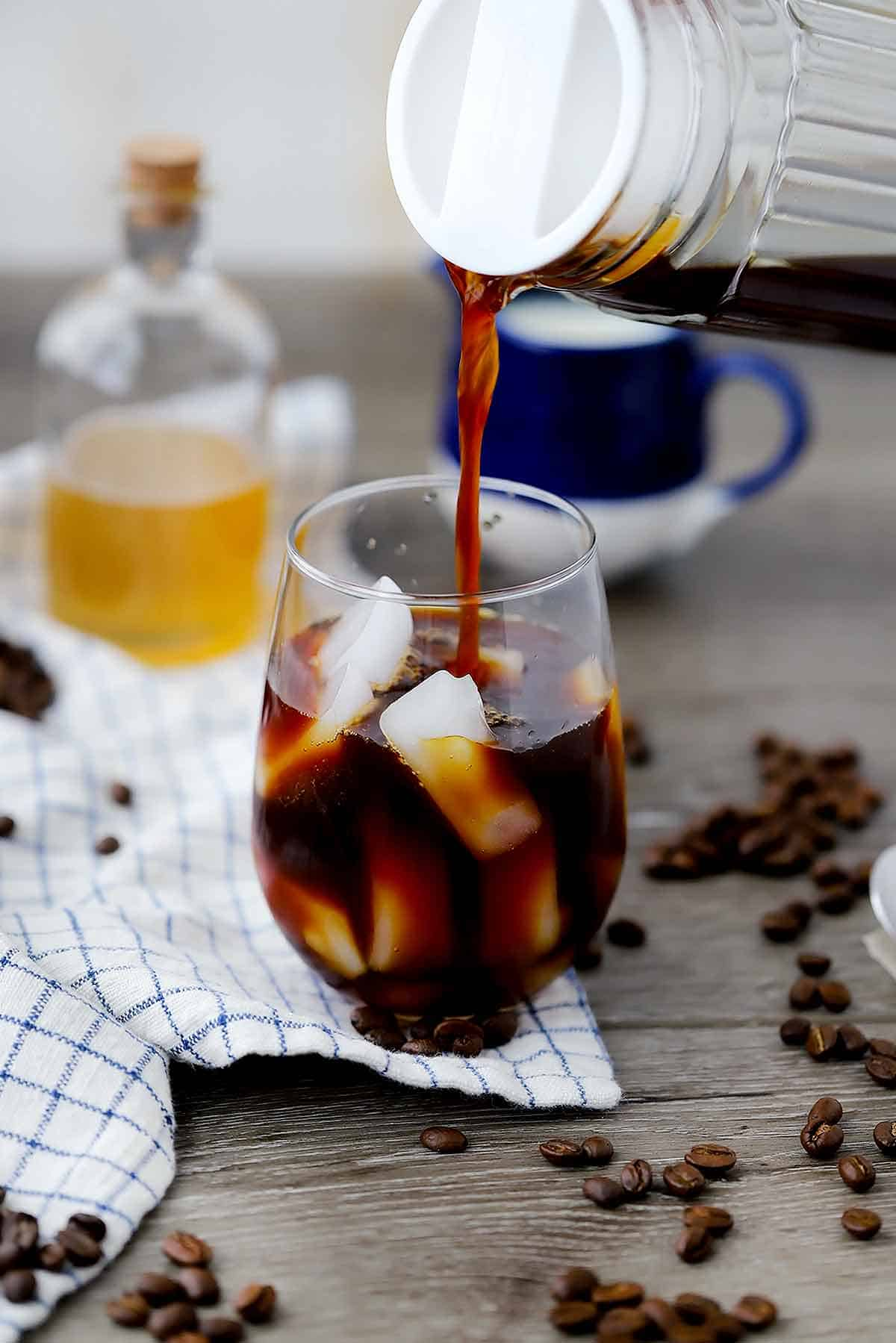 Pouring cold brew coffee over ice.