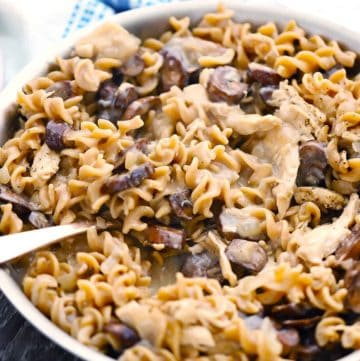 A skillet with healthy chicken and mushroom stroganoff and a spoon scooping some out.