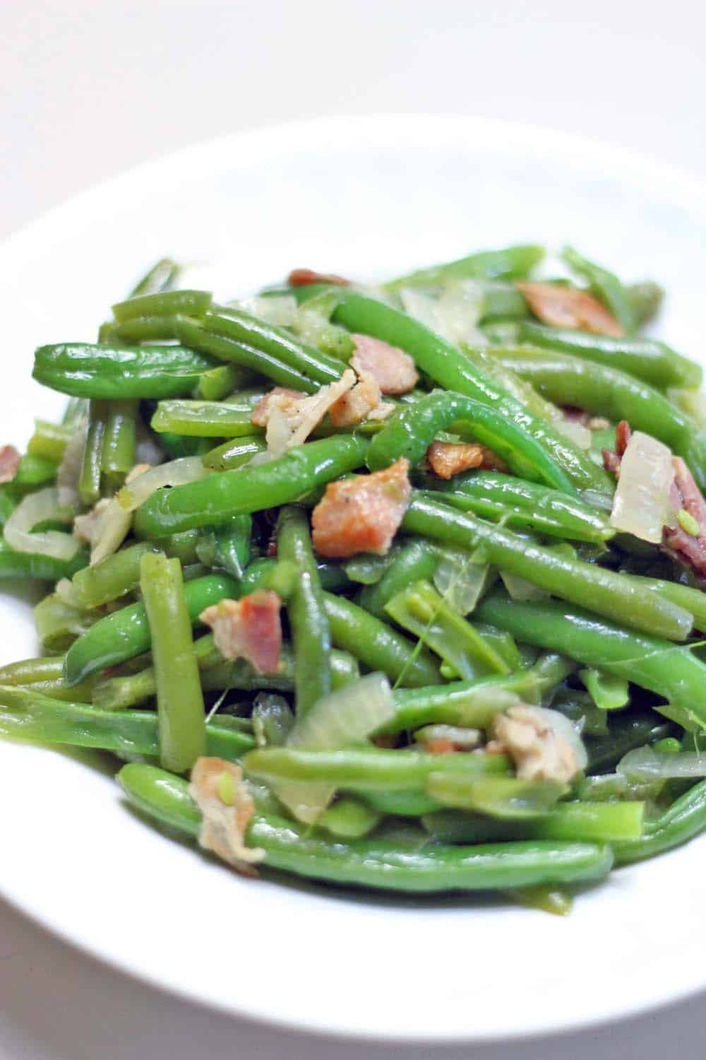 These Southern Style Green Beans are easy and melt-in-your mouth delicious- they're smoky from the bacon and super savory from simmering to perfection in chicken broth! YUM.