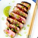 A plate with seared ahi tuna steak, chopsticks, a lime wedge, and scallions.