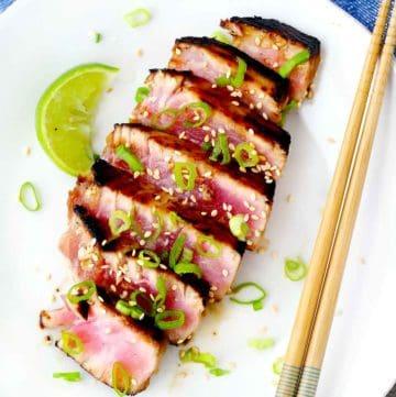 A plate with seared ahi tuna steak, chopsticks, a lime wedge, and scallions.