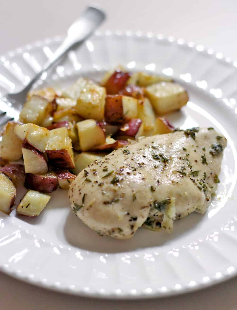 This healthy Whole30 and Paleo friendly rosemary and garlic roast chicken and potatoes dinner is SO easy, SO tasty, and uses only FOUR ingredients!