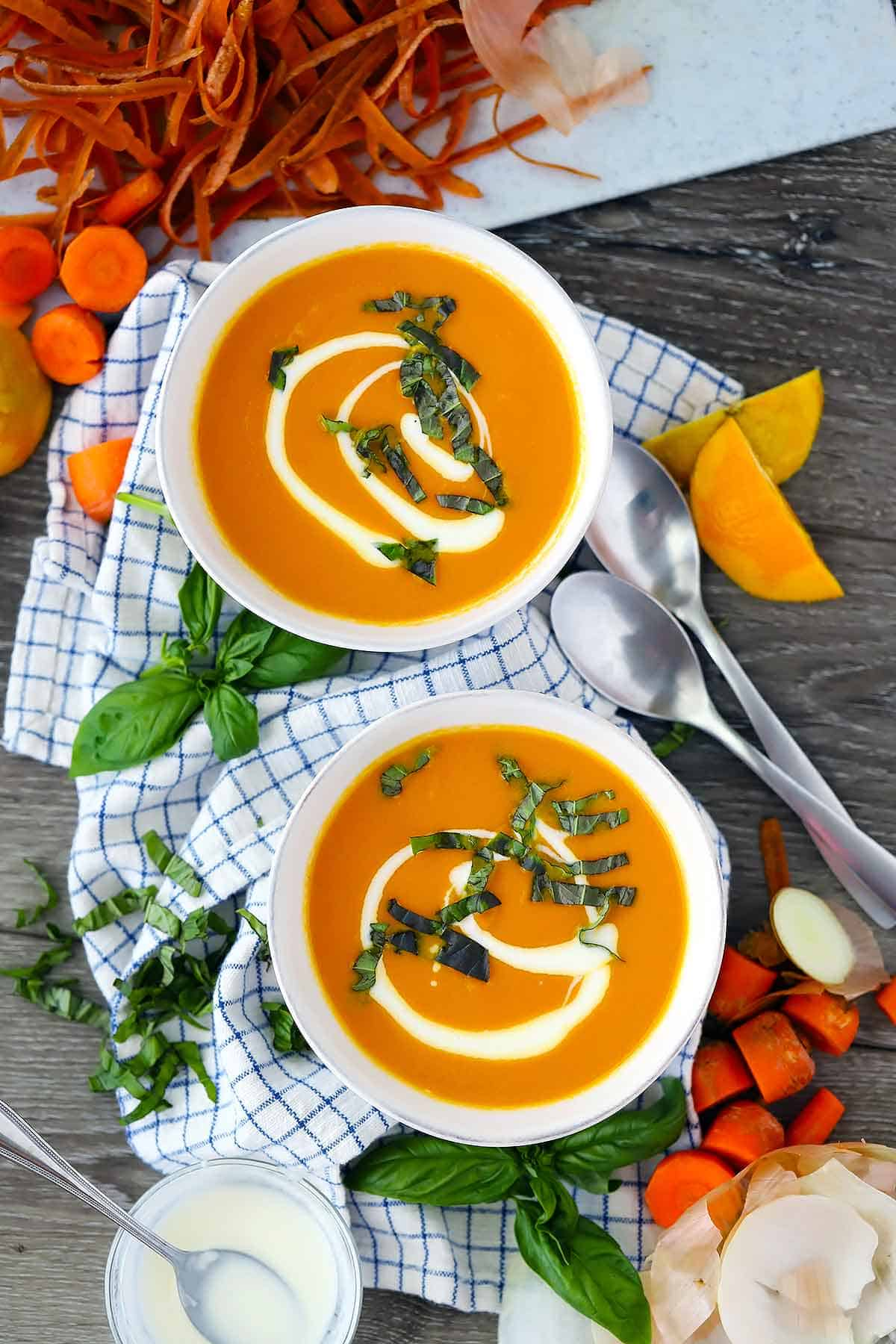 Flatlay of two bowls of carrot ginger soup.