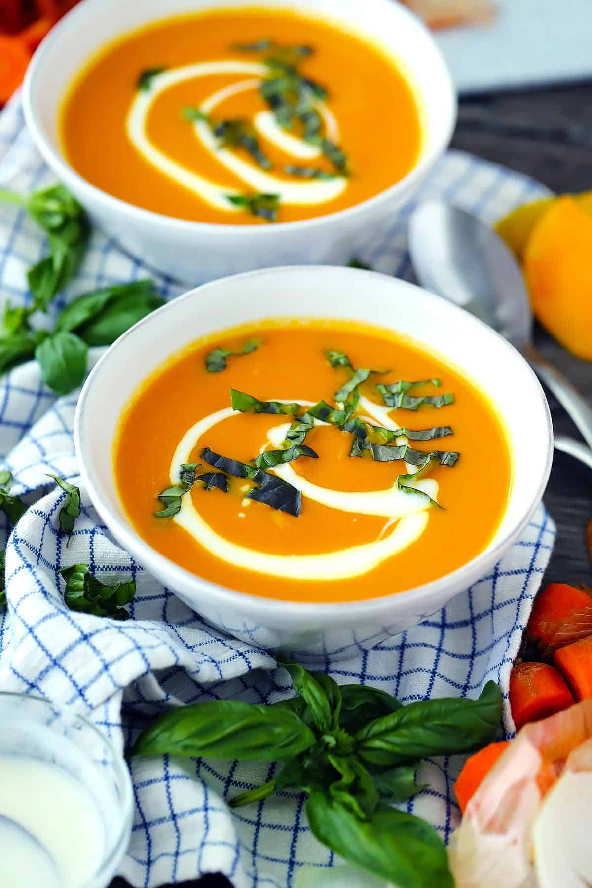 A white bowl filled with carrot soup.