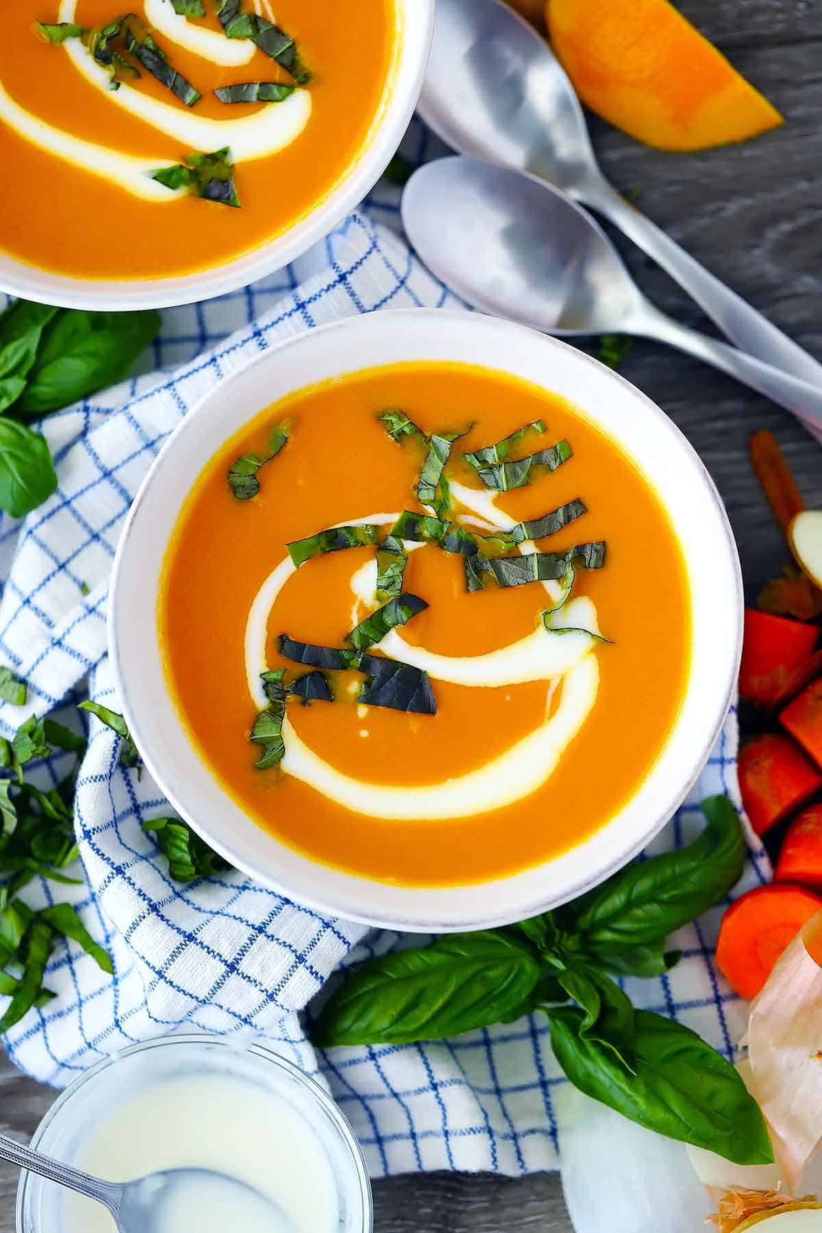 An overhead photo of a bowl of carrot ginger soup garnished with fresh basil.